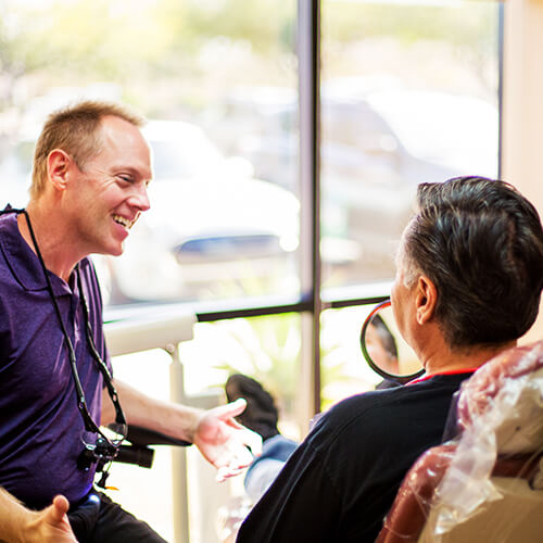 Dr. Walker, a dentist in Chandler, AZ, chatting with a patients about their needs