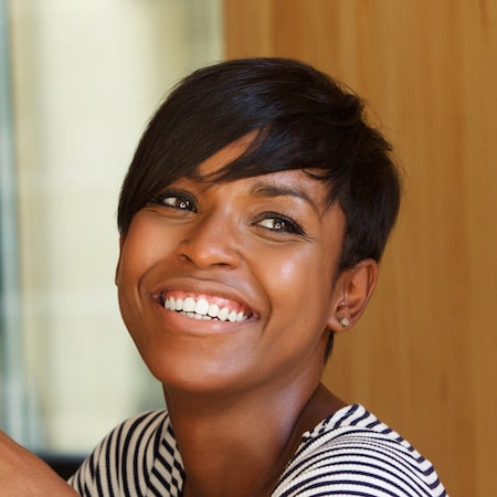 Woman with short hair smiling after her dental bridge from Dr. Walker