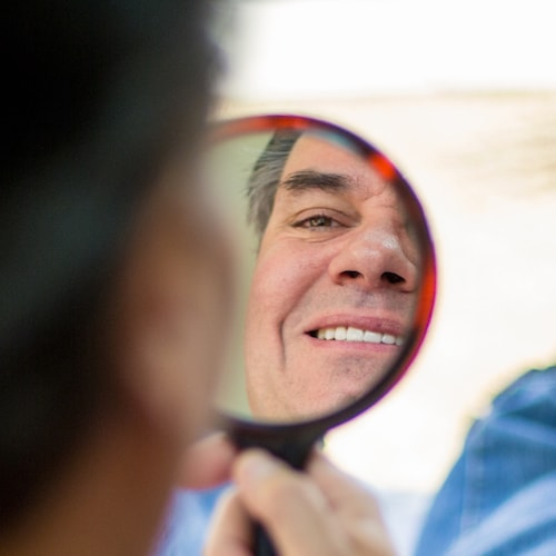 Man looking into a mirror at his new porcelain veneers