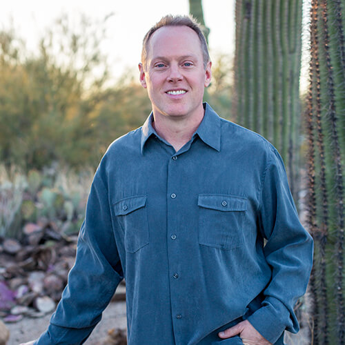 Dr. Robert Walker Jr., a dentist in Chandler, AZ, standing in front of a cactus and smiling