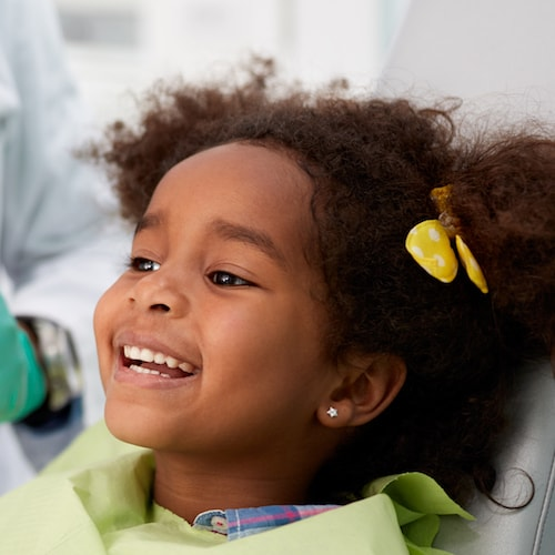 Child smiling while in the dentist chair and enjoying children's dentistry