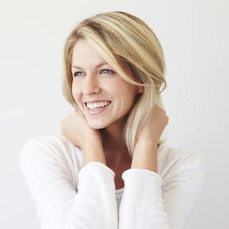 Woman looking away with her hands on her neck and smiling