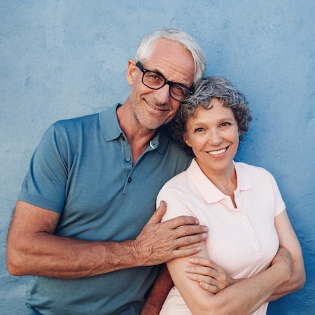 Older couple smiling in front of a blue wall after their root canal therapy
