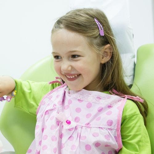Little girl smiling while wearing a pink dental bib