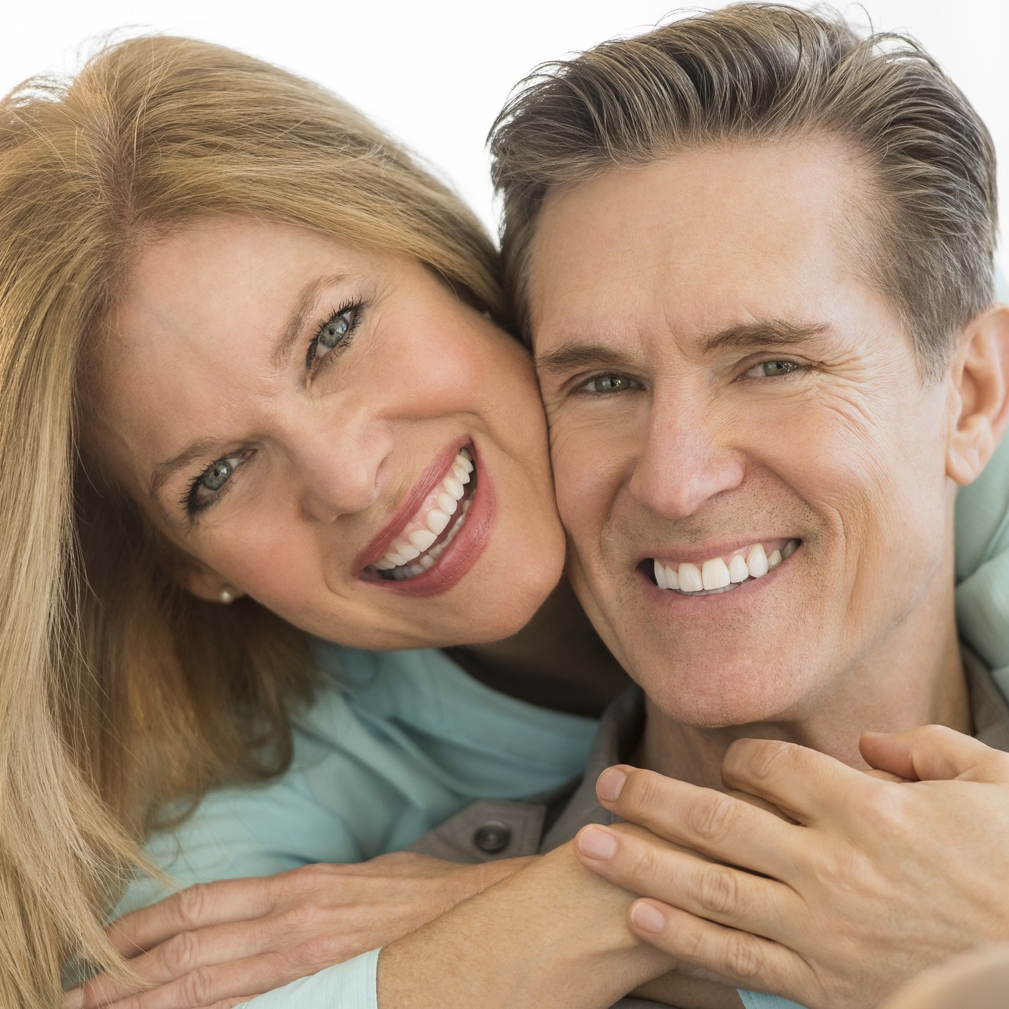 Happy woman embracing man on sofa at home confidently smiling with All-on-4 dental implants.