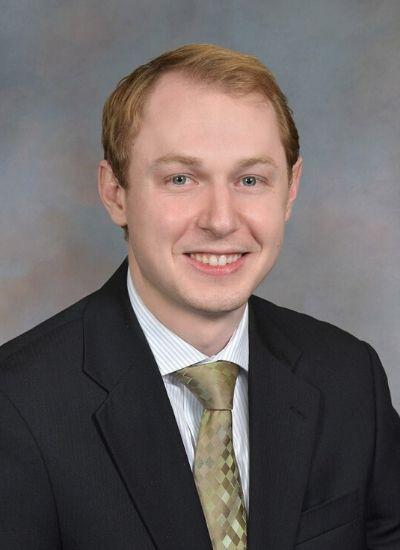 Dr. Brandt Hansen in a black suit